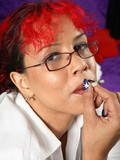 Red haired female smokes in the office then strips and dildos her beaver