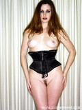 Brunette in tight fit black corset shamelessly shows her trimmed pussy and tits