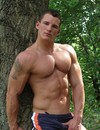 Sporty muscled man gets topless and poses while walking the forest in the middle