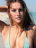 Cuddly Adriana in really skimpy blue bikini plays on the beach and goes topless