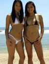 Two sexy oriental babes turn around showing their tits and booties on the beach