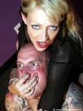 Tattooed shaved headed man gets smothered by dominating blonde in the violet room
