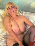 Blonde woman in black stockings takes off her red lingerie and shows her giant knockers