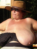 Fat mature woman in hat pulls her ugly gigantic boobs out of her bra on a bench outdoors