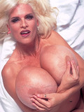 Mature blonde Busty Dusty demonstrates her huge boobs and applies soap to them