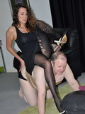 Long legged mistress in black dress and tights gives footjob to her fat slave
