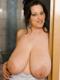 Topless dark haired woman exposes her unthinkably big natural tits in the bathroom