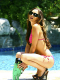 Mouth-watering slim brunette babe in sunglasses takes off her pink bikini in the pool