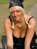 Heavy titted pigtailed mature blonde in bandanna and sunglasses poses on a bike