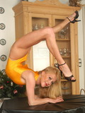 Gymnast Karen in yellow uniform shows off her flexible body and beautiful slim l