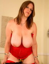Chubby girl in red and black displays her huge natural tits and shaved puffy pussy
