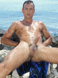 Nude oiled up sexy guy demonstrates his long cock in the sun on the rocky beach