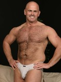 Shameless hairy aged man with charming smile takes off his tight briefs to show