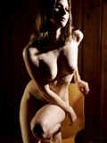 Shy auburn girl with mighty fine body poses completely nude in the semi-dark