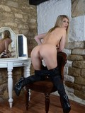 Naughty blonde in high boots and stockings demonstrates her slit and breasts