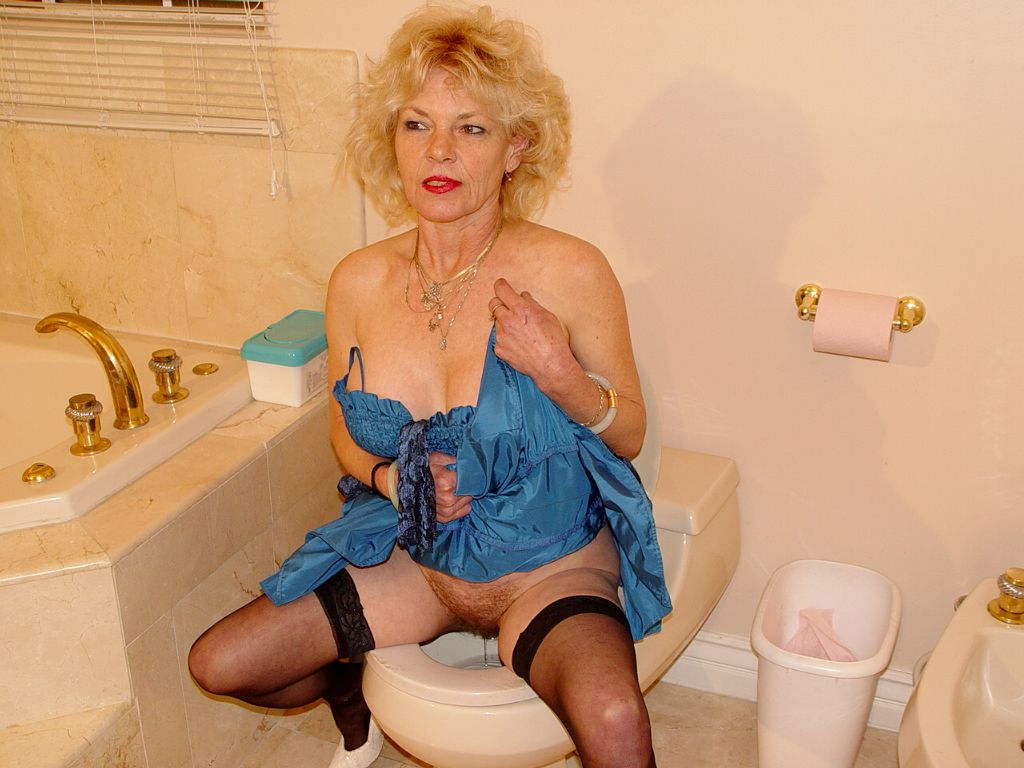 wrinkled granny in blue dress and black stockings peeing with legs