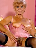 Wrinkled elderly woman in black nylons and pink silk corset shows her hairy mature cunt