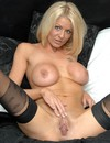 Busty glamorous blonde milf in black stockings demonstrates her pussy invitingly