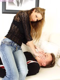 Chick in blue jeans and black blouse smothers guy sitting on his chest