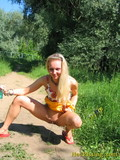 Smiling blonde spreads her legs and pees in the middle of the country road