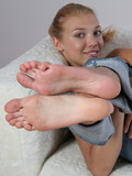Sweet barefoot girl in jeans Kamila shows off her soles and toes on the bed