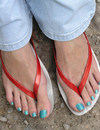 Girl in jeans and flip flops demonstrates her toes and blue toenails outdoors