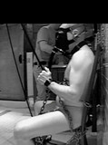 Hidden camera features naked masked prisoner with tied hands getting his dick tugged
