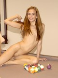 Slim girl with long hair strips nude in the middle of the pool table and plays with her love hole