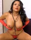 Delicious brunette Darlene in sexy long red gloves puts her hands on her huge boobs