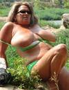 Chubby woman in green swimming suit displays her gigantic fat knockers