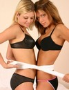 Two sassy teen babes in black underwear blindfold and play with each other