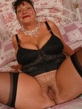 Mature brunette in black lingerie and stockings spreads her legs and shows her many times used cunt