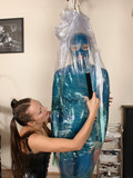 Latex girl gets mummified by long haired kinky mistress in the middle of the room