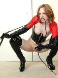 Redhead lady in black and red latex outfit shows her shaved pussy and pink nipples