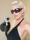 Charming long haired blonde dressed in black loves posing with gun in hands