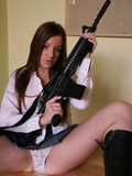 Brunette in blouse, skirt and boots flashes her white panties while posing with gun