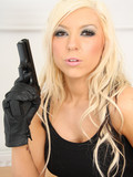 Flirtatious blonde dressed in black poses with gun showing nothing but her serious face