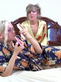 Two lustful blondes make themselves comfy on the bed and polish their erect clits