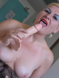 Mature blonde in nylon stockings opens her legs  to insert dildo in her cunt