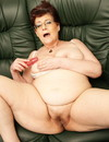 Four-eyed granny strips naked and fills her well experienced pussy with dildo