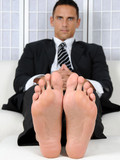 Handsome middle aged man Cody in office uniform demonstrates his nice feet