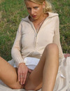 Lusty blonde bares her tits and pussy sitting on the lawn and plays with a big d