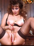 Naughty mature in black lingerie rubs big glass dildo on her shaved pussy
