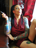 Tattooed transsexual brunette Nicole Dupre smokes a cigarette and bares her amaz