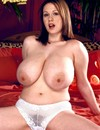 Delicious lady with massive natural breasts gets completely naked on the bed