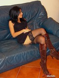 Leggy brunette in nylons takes off her high boots in front of the camera