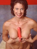 Sexy mature lady with nice juicy beasts fucks her shaved cunt with red dildo in front of you