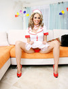Leggy young blonde in red high heels shows her naughty bits with smile on her alluring face