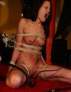 Tied up slave brunette in red shoes gets her bald tight pussy whipped ruthlessly