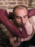 Obedient older man licks young topless brunette's pantyhosed legs and feet